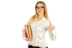 Blonde Aufstellung mit Büchern und Lächeln Lizenzfreie Stockfotos