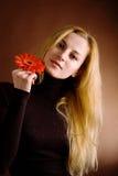 Blonde Aufstellung mit einer roten Blume Stockfotos