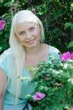 Blonde Aufstellung nahe dem Busch mit Blumen Lizenzfreies Stockfoto