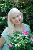 Blonde Aufstellung nahe dem Busch mit Blumen Stockfoto