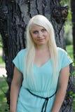 Blonde Aufstellung nahe einem Baum Stockfoto