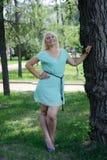Blonde Aufstellung nahe einem Baum Stockfotos