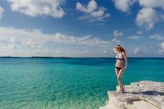Blonde Aufstellung am Rand eines Klippe karibischen Meeres Lizenzfreie Stockfotos