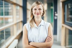 Blonde authentieke onderneemster met het gekruiste wapens glimlachen stock afbeeldingen
