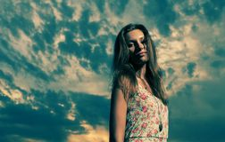 Blonde aux cheveux longs contre le ciel nuageux images libres de droits