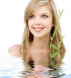 Blonde aux yeux bleus avec le bambou dans l'eau image libre de droits