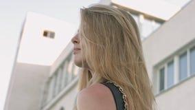 Blonde aux yeux bleus dans la robe en cuir noire posant contre le bâtiment blanc urbain clips vidéos
