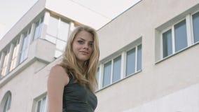 Blonde aux yeux bleus dans la robe en cuir noire posant contre le bâtiment blanc urbain banque de vidéos