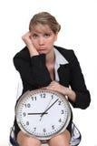 Blonde avec l'horloge semblant ennuyée Photo libre de droits