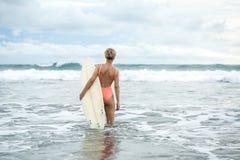 Blonde avec la planche de surf sur la plage Images stock