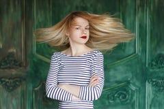 Blonde avec les lèvres rouges dans la chemise rayée sur un fond vert Images stock