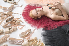 Blonde ballerina lies in studio. Attractive ballerina lies on the colorful tutus on the white floor in the studio. She wears a light top and holds pointe shoes Royalty Free Stock Image