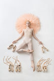 Blonde ballerina lies in studio. Tender ballerina lies in passe on the peach tutu on the white floor and holds pointe shoes in the studio. She wears a light Royalty Free Stock Photography