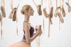 Blonde ballerina with pointe shoes. Cute ballerina in a violet top and a peach tutu stands sideways on the light background in the studio. Around her there are royalty free stock photos