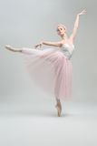 Blonde ballerina in studio. Elegant ballerina stands on pointe on the gray background in the studio. She wears a dance wear with white top and a rose skirt and royalty free stock photos