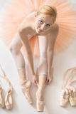 Blonde ballerina in studio. Smiling ballerina sits on the white floor and dresses a beige pointe shoe in the studio. She wears a light dance wear and a peach Stock Photo