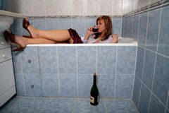 Blonde in bathroom in clothes with wine Stock Photography