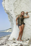 Blonde on a beach. Beautiful girl a blonde is on a stone beach near a sea Stock Image