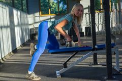 Blonde beatifull girl in the blue leggings and green t-shirt smile and push weight on the bench on the background royalty free stock photos