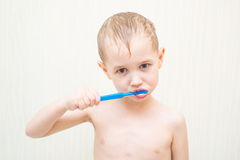 Blonde beautiful boy brushing his teeth in the Royalty Free Stock Images