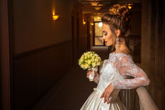 Blonde beautiful bride in fashionable wedding dress with bouquet of roses. In hands royalty free stock photo