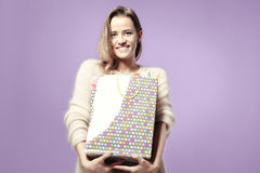 Blonde beautiful caucasian woman happy with present paper bags in hands. Wearing warm sweater, happy emotions. Royalty Free Stock Photography