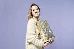Blonde beautiful caucasian woman happy with present paper bags in hands. Wearing warm sweater, happy emotions. Stock Photography