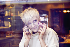Blonde beautiful caucasian woman wearing white sweater sitting in cafe near window. stock images