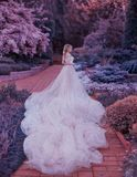 Blonde, with a beautiful elegant hairdo, walks in a fabulous blooming garden. Princess in a luxurious light pink dress stock photos