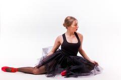 Blonde beautiful girl in black tutu dress doing gymnastic split. Royalty Free Stock Photo