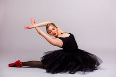 Blonde beautiful girl in black tutu dress doing gymnastic royalty free stock photos