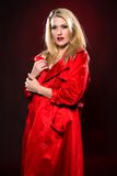 Blonde. Beautiful slender blonde woman in a red raincoat Stock Images