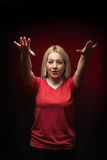 Blonde beautiful woman football fan chanting with both arms raised in red  T shirt Stock Photo