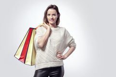 Blonde beautiful woman with shopping paper bags on shoulder. Calm emotions, caucasian face, sweater. Stock Images
