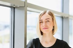 Blonde beauty business woman portrait look. Blonde beauty businesswoman portrait look at camera on window background Stock Photo
