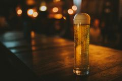 Blonde beer pint on a wooden table, with low light. Blonde beer pint on a wooden table, with pub lights in the background at night, and copy space in left side stock photography