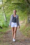 Blonde behaarte Frau, die in Wald geht Stockfoto