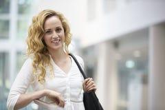 Blonde behaarte junge Frau, die im modernen Innenraum sich lehnt Stockfotografie