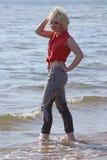 Blonde behaarte junge Frau am Strand Stockbild