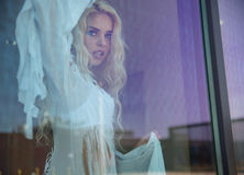 Blonde behind the huge window Royalty Free Stock Images