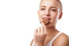 Blonde beißende Schokolade der jungen Frau lokalisiert Lizenzfreies Stockfoto