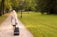 Blonde Berufsfrau, die einen Koffer zieht Stockbilder