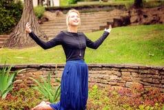Blonde betende und anbetende Dame Stockfotografie