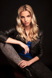 Blonde biker woman in leather jacket resting hand on knee Royalty Free Stock Photos