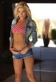 Blonde Bikini Model. Beautiful blonde fashion model wearing colorful bikini top posing alone on sunny day Stock Photography
