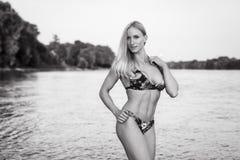 Blonde Bikinifrau in einem Fluss Stockfotos