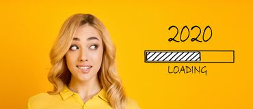 Blonde biting her lip and looking at 2020 loading process. Waiting for new year. Blonde biting her lip and looking at 2020 loading process, yellow panorama stock image