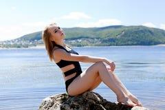 Blonde in black bathing suit sitting on large rock Stock Photo
