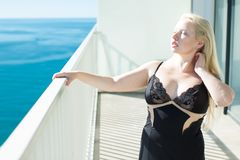 Blonde woman in a black corset on the balcony overlooking the sea. Blonde in a black corset on the balcony overlooking the sea Royalty Free Stock Photography