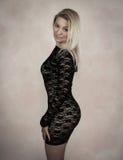 Blonde in black dress. Blond woman in lace mini black dress royalty free stock photo